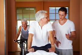 Fitness coach explaining spinning exercises to two senior people