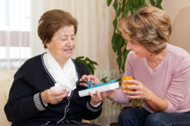 caregiver giving a medicine to an old woman